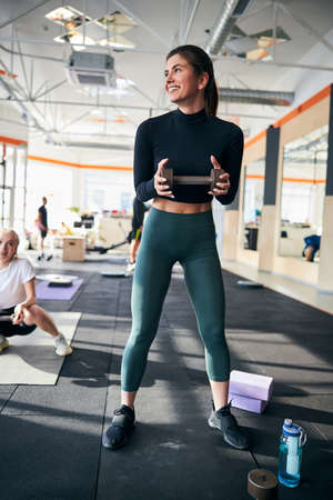 Full-length photo of an optimistic young lady holding a dumbbell and looking to the side with a wide smile