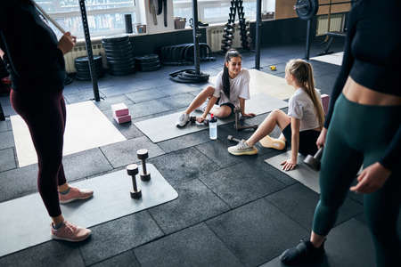 Selective focus photo of two lovely young women sitting on fitness mats and chatting while taking break from working out Archivio Fotografico