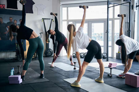Sporty young women with dumbbells in hands reaching to the sides while having a gym class with an instructor