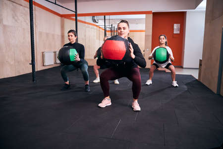 Three determined young women holding fitness balls and doing squats
