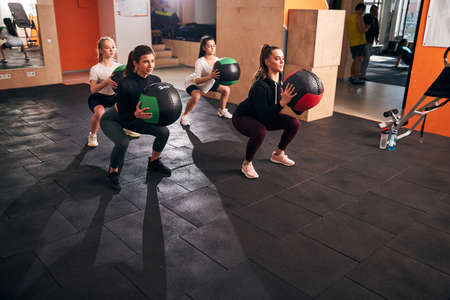 Strong young ladies holding big fitness balls and doing deep squats at well-equipped gym