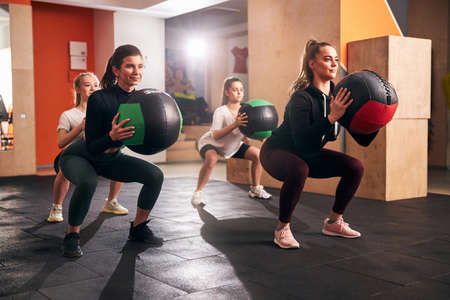 Energetic young women squatting while holding big fitness balls for extra weight