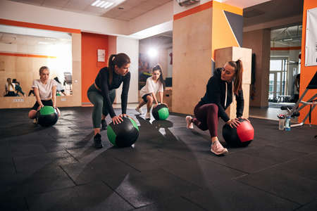 Group of young motivated women exercising on gym floor and using big fitness balls Archivio Fotografico