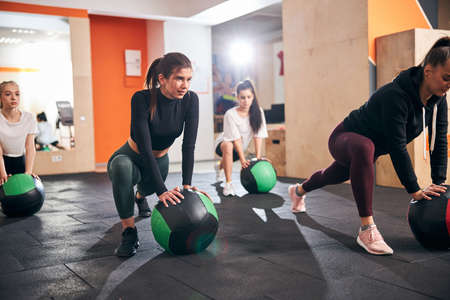 Slender young women exercising on gym floor and using special fitness balls for their workout Archivio Fotografico
