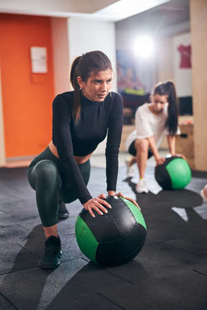 Selective focus photo of a beautiful concentrated woman doing exercises with fitness ball at the gym