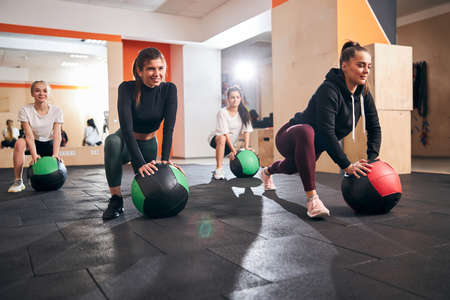 Active young women smiling and feelling energized while exercising with special fitness balls Archivio Fotografico