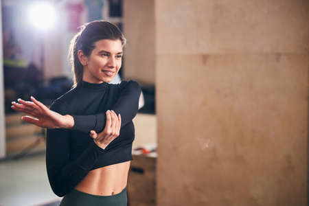 Copy-space photo of a young brunette lady giving her arm muscles a proper stretch after a productive workout Archivio Fotografico