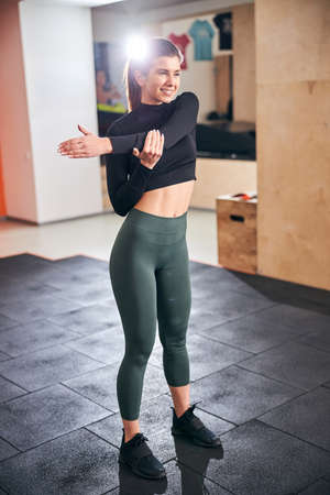 Full-length photo of slim brunette lady smiling and stretching her arm muscles while doing exercises at gym Archivio Fotografico