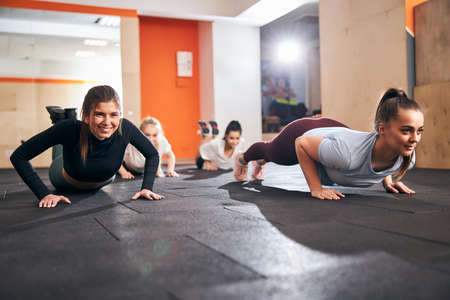 Smiley young women feeling powerful while doing narrow push-ups at a gym floor