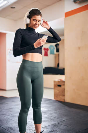 Slim brunette lady wearing headphones and looking at her smartphone while standing at gym