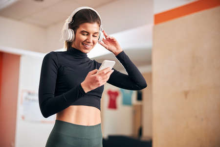 Waist-up photo of fit brunette woman smiling while wearing headset and looking at her phone