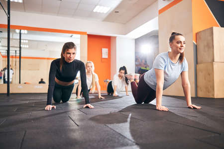 Positive young ladies doing push-ups from their knees while working out at the gym Archivio Fotografico