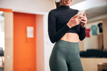 Copy-space cropped photo of fit young lady smiling while holding smartphone and standing at the gym