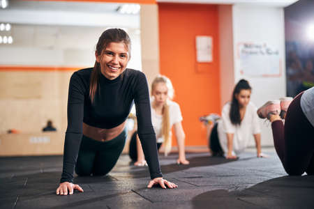 Selective focus photo of attractive brunette lady doing push-ups with her friends and looking at the camera Archivio Fotografico