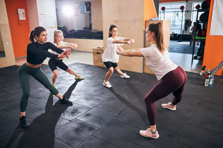 Concentrated young women in sporty outfits doing deep squats at gym together Archivio Fotografico