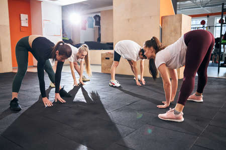 Group of fit athletic women reaching for their toes while stretching together at the gym Archivio Fotografico