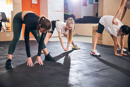 Three flexible young women reaching for the floor while bending down during their gym stretching session