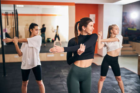 Three slim athletic young women warming up before doing some serious physical exercises