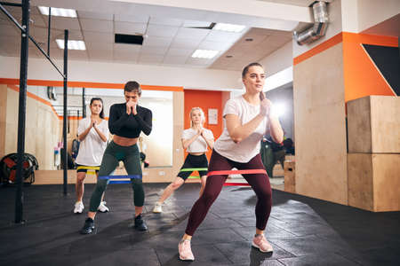 Slender ladies using resistance bands fot their workout at the gym Archivio Fotografico