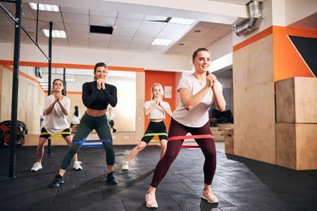 Excited young female athletes keeping themselves in shape by regular exercising with resistance bands