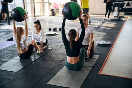 Restless young ladies working on their abs and core while exercising in pairs at the gym
