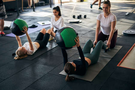 Hard-working athletic ladies working out in pairs and backing each other up in abs exercises Archivio Fotografico