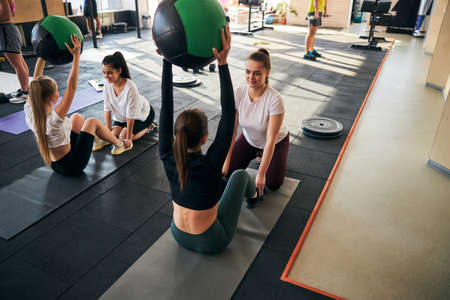 Active young women with fitness balls in hands lifting their upper body and doing abs exercises