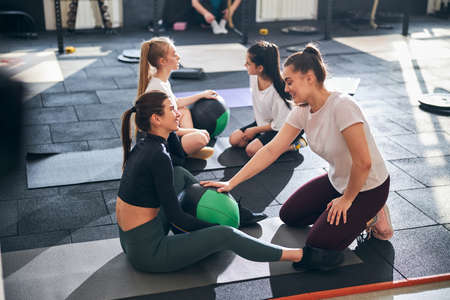 Cheerful active women working out with fitness ball and doing abs crunches together