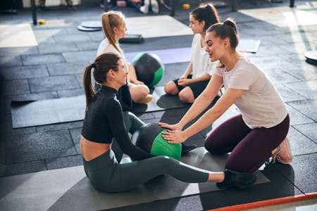 Active and athletic young ladies exercising in pairs and assisting each other while working out