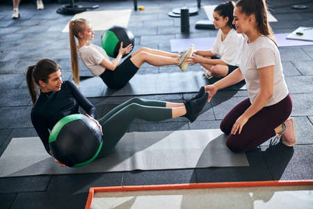 Ambitious young women doing abs exercises in pairs and taking turns with a fitness ball