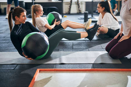 Athletic young women doing abs twists while holding fitness balls Archivio Fotografico