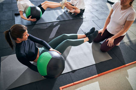 Cropped photo of slim fit women using fitness balls and doing abs twists