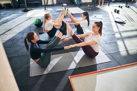 Cheerful young women having their legs up while doing partner exercises on the gym floor