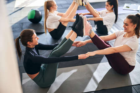 Fit positive ladies in athletic outfits exercising and stretching on gym floor