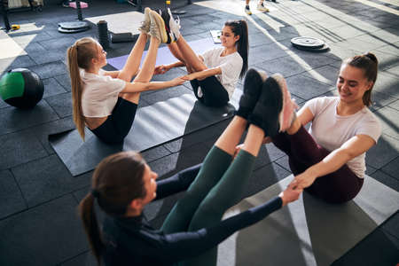 Group of young sporty women exercising balance in pairs while sitting on gym mats with their legs up