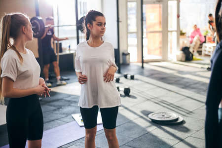 Adolescent women in sporty outfits taking a break between exercises sets at well-lit gym