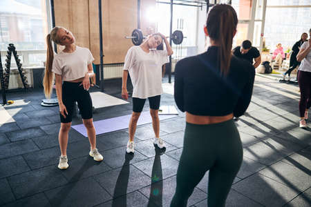 Rear-view photo of a professional couch watching women warm up their neck muscles before working out