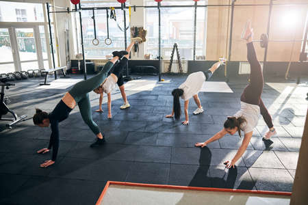 Group photo of fit young ladies doing an advanced downward dog pose at gym
