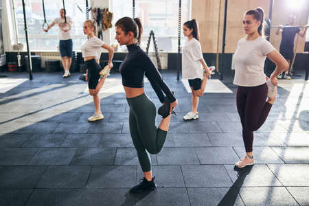 Motivated young ladies stretching their leg muscles after a productive gym workout Archivio Fotografico