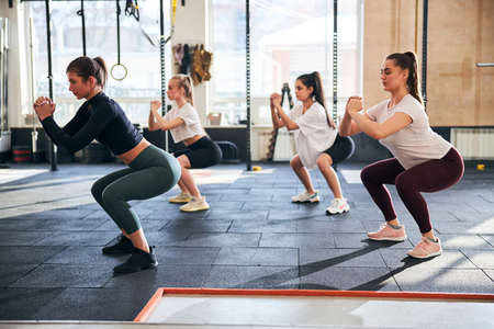 Strong fit young women looking determined while performing squats at a sunlit gym Archivio Fotografico