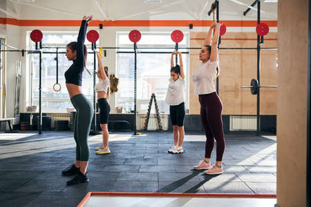 Group of slim young women reaching their arms towards the ceiling while stretching after a productive workout