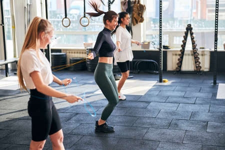 Joyous young women smiling and exercising with skipping ropes at sunlit gym
