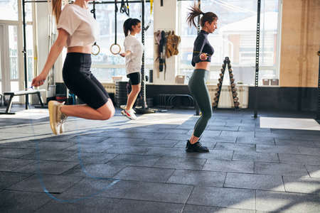 Energetic young women skipping ropes while exercising at the gym Archivio Fotografico