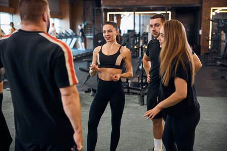 Experienced sports instructor talking to visitors of gym