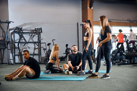 Group of sporty people in athletic outfts posing at gym