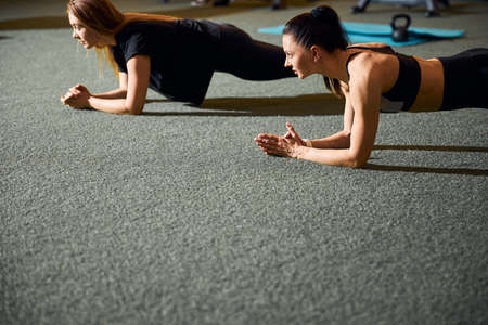 Two fit women exercising in endurance and doing planks
