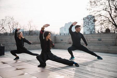 Three people doing tai chi deep side lunge