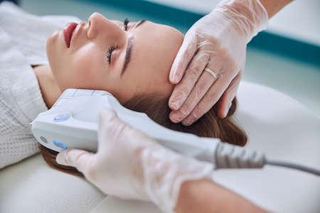 Relaxing charming female in white bathrobe enjoying ultrasound contour face plastic in spa center
