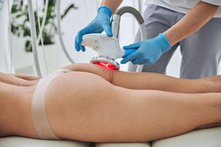 Unrecognized lady lying on medicine table while getting anti-fat treatment in spa salon Stock fotó