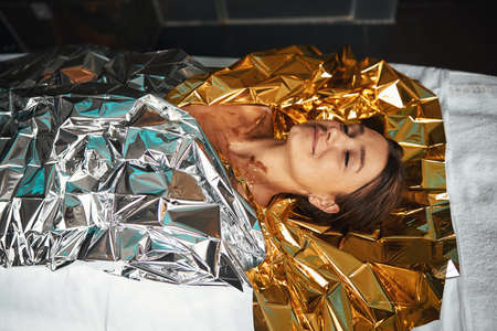 Happy smiling positive female enjoy spa procedure while wrapping around with foil in spa center